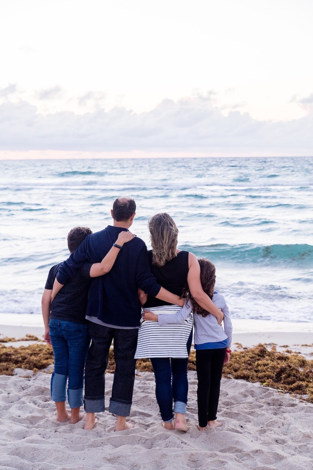 family hugging at the beach